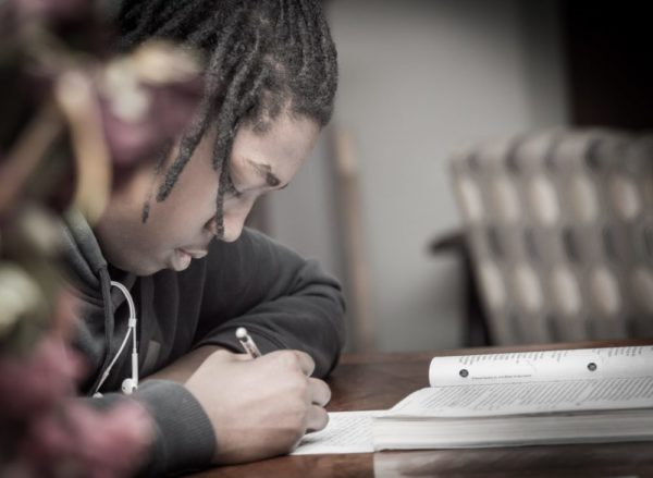 student writing an essay in class